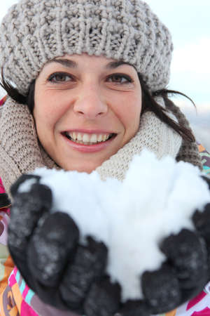 all smiles: woman all smiles at ski resort with snow in hands