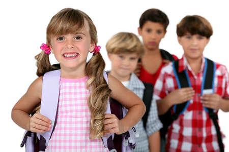cola mujer: niños vestidos con sus mochilas escolares Foto de archivo