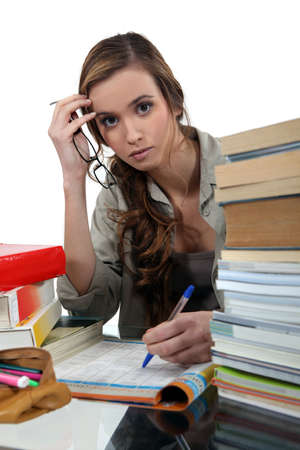 revision book: Student surrounded by books