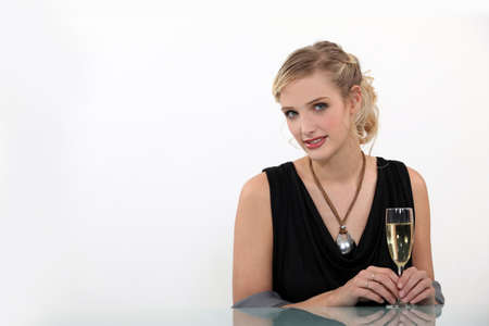 moderation: shy blonde with flute of champagne against white background