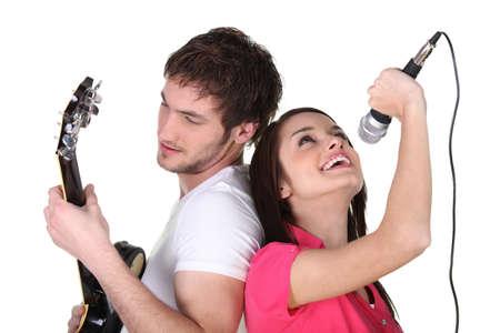 people singing: two people singing and playing guitar