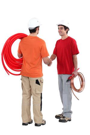 journeyman technician: duo of plumbers shaking hands
