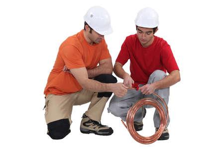 koperen leiding: Twee loodgieters met koperen buis