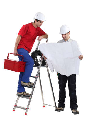 architect unfolding blueprints and electrician on ladder photo