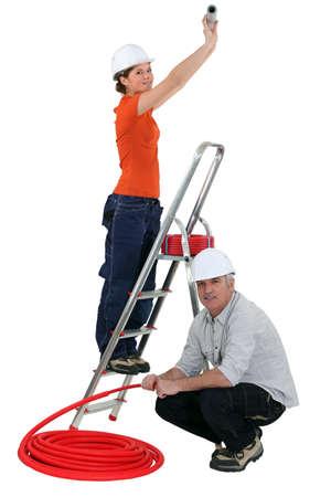 tradespeople: A team of tradespeople installing plumbing Stock Photo