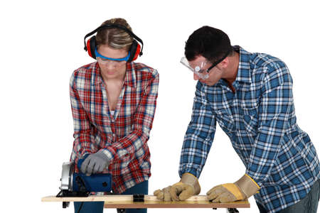 Tradespeople cutting a wooden plank with a circular saw photo