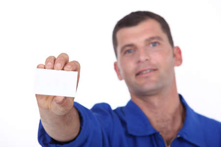 Man in blue overalls holding up a blank business card photo
