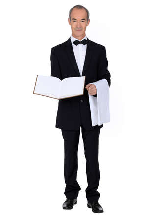60 years old: 60 years old well dressed waiter is presenting a visitor book or a menu