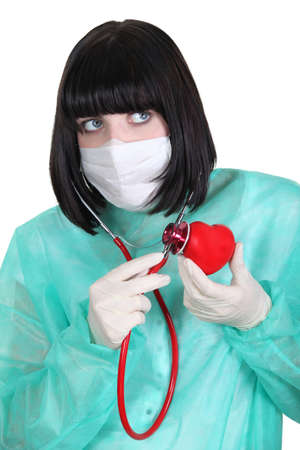 plastic heart: Doctor listening to a plastic heart with a stethoscope