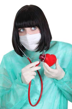 plastic heart: Medico l'ascolto di un cuore di plastica con uno stetoscopio