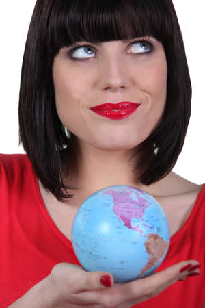 Woman in red holding planet earth photo