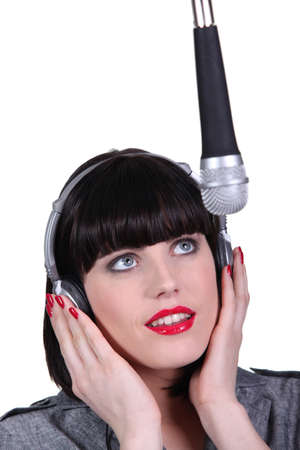 Woman singing into a studio microphone photo
