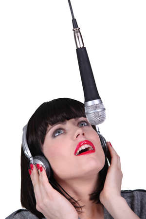 transducer: Woman singing into a microphone Stock Photo