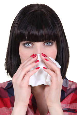 achy: Woman blowing her nose Stock Photo