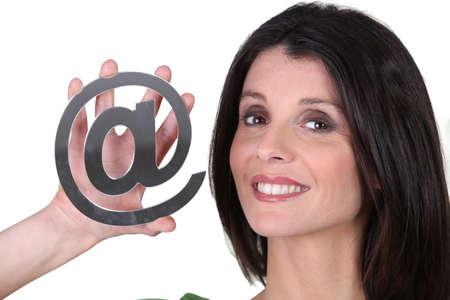 arobase: Brunette holding at symbol