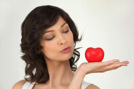 tilted: Woman with a heart laying on the palm of her hand Stock Photo
