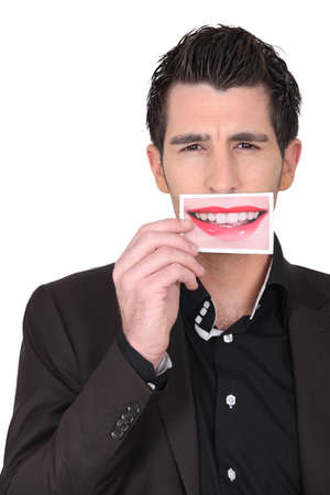 dark-haired man holding picture of female mouth smiling Stock Photo - 17385612