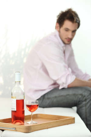 depressed man looking a wine bottle photo