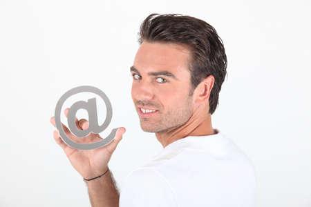arobase: Man holding at symbol Stock Photo