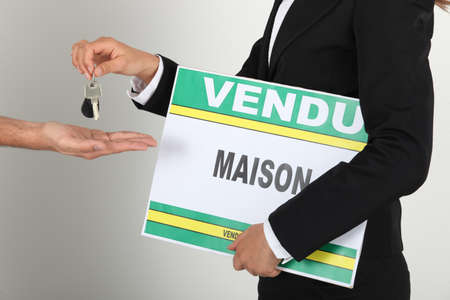 Estate-agent holding sold sign and handing keys to client photo