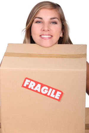 determined: head of blond girl leaning on moving cardboard Stock Photo