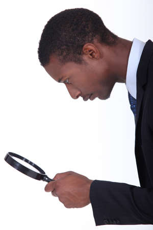 attest: black man looking through a magnifying glass