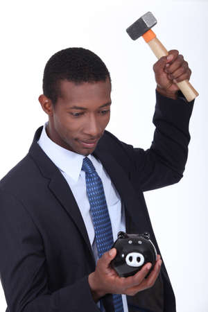 Man breaking a piggy bank open with a hammer photo