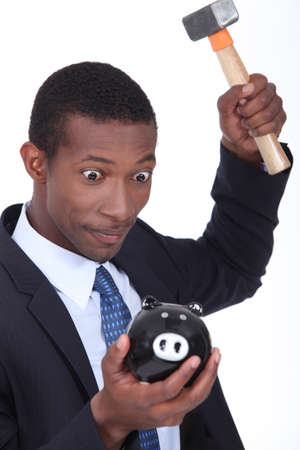 Insane man smashing open a piggy bank with a hammer Stock Photo - 17386069
