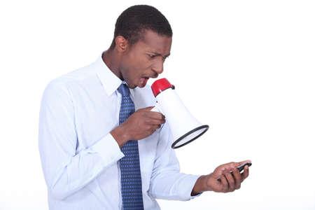 vexation: Man shouting through a megaphone at a cellphone Stock Photo