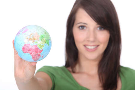 young woman holding out world globe photo