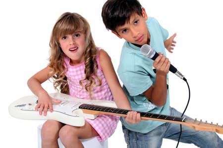 child singing: Kids pretending to be in a rock band Stock Photo