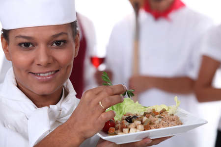 joining services: young chief cook showing a salad dish