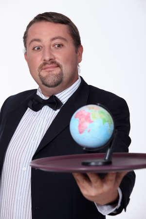 bringing: man bringing the globe on a plate