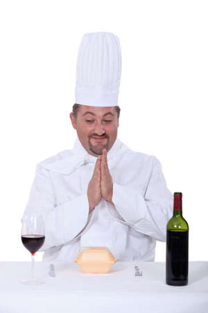 hesitancy: chef sitting between glass of wine and bottle of wine and facing hamburger