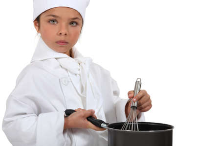 a little girl dressed in chief cook uniform is cooking photo
