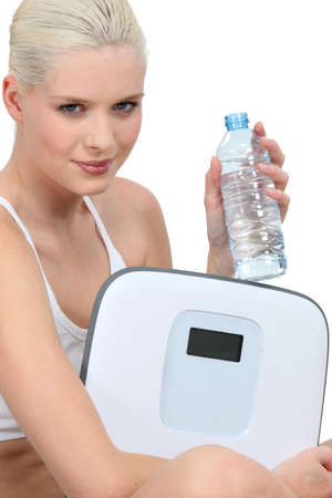 weight reduction plan: Young woman with a bottle of water and a pair of scales