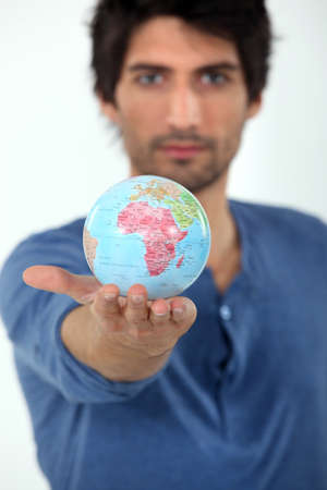 encyclopedic: Man holding the world in the palm of his hand Stock Photo