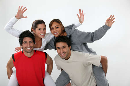 horseplay: two young men carrying women on their backs Stock Photo