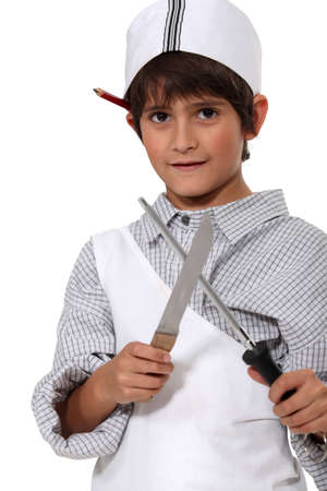 grown ups: Young boy dressed as a butcher sharpening a knife Stock Photo