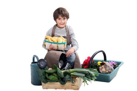 niño recogiendo verduras frescas en el jardín