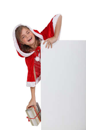 Child in a Santa costume with a board left blank for your message Stock Photo - 17385277