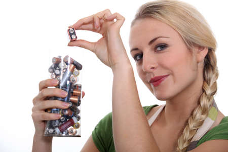 smug: Blond woman recycling used batteries