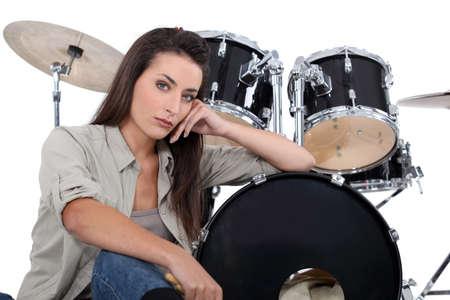 drum kit: Brunette sat in front of drum kit Stock Photo