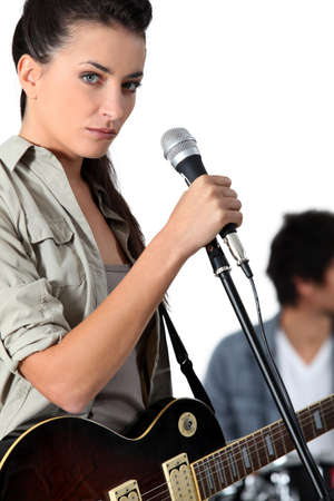 Young woman singer holding microphone photo