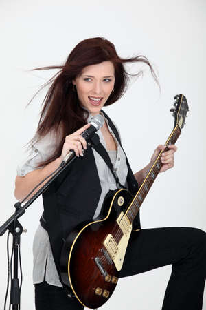 young woman playing guitar and singing photo