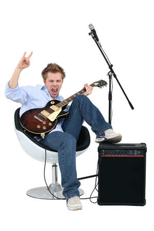 Young man with guitar playing rock music photo