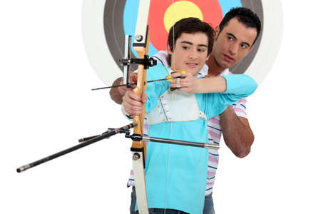 Man and a teenager practicing archery photo