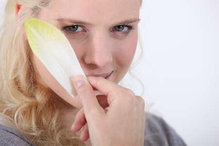 escarola: Joven rubia con la hoja de endibia Foto de archivo