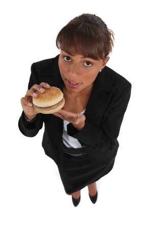 gullible: Businesswoman eating a hamburger