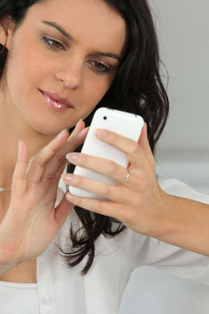 savvy: Young woman using a touch screen phone